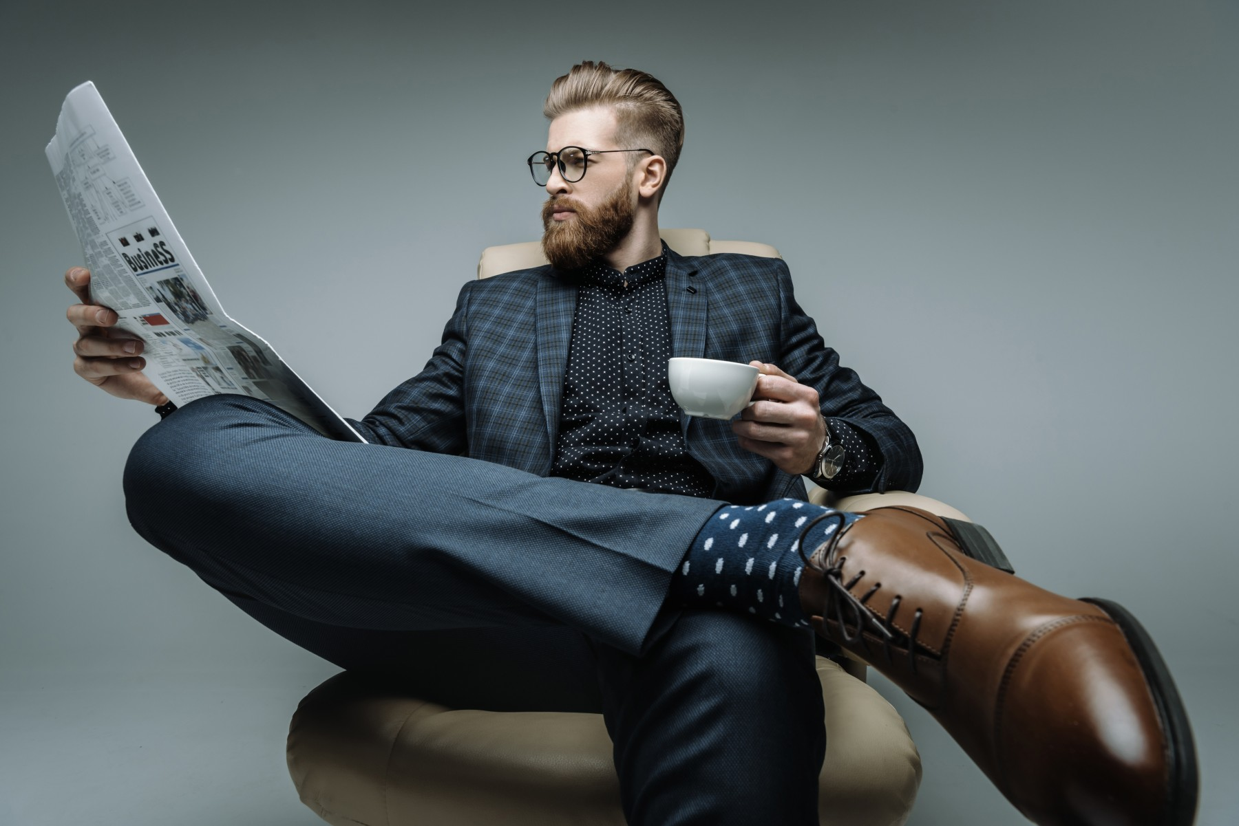 stylish businessman with cup of coffee reading newspaper on grey
